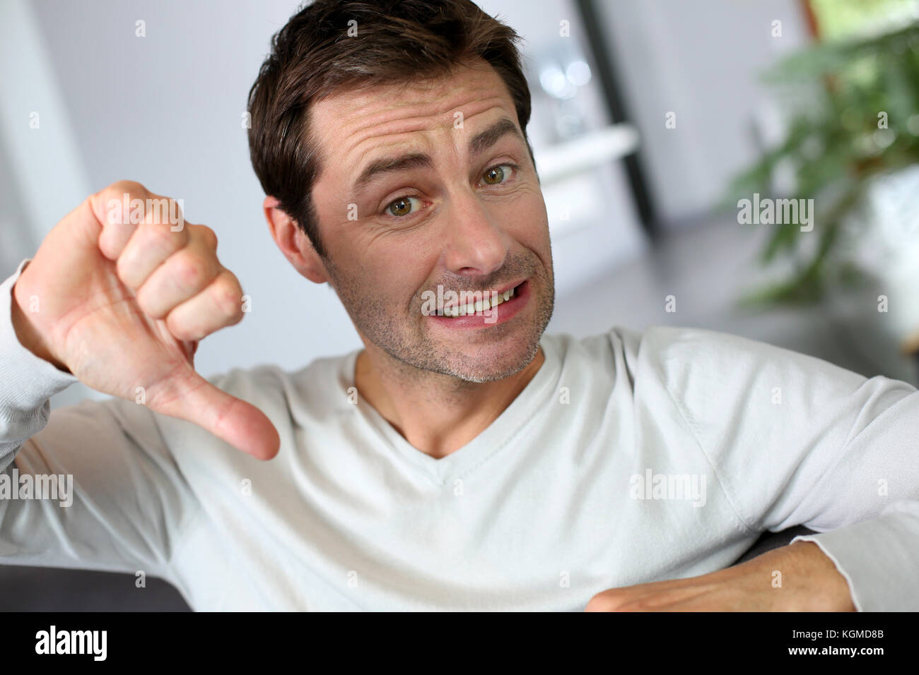 Hombre descontento mostrando pulgar abajo Imagen De Stock