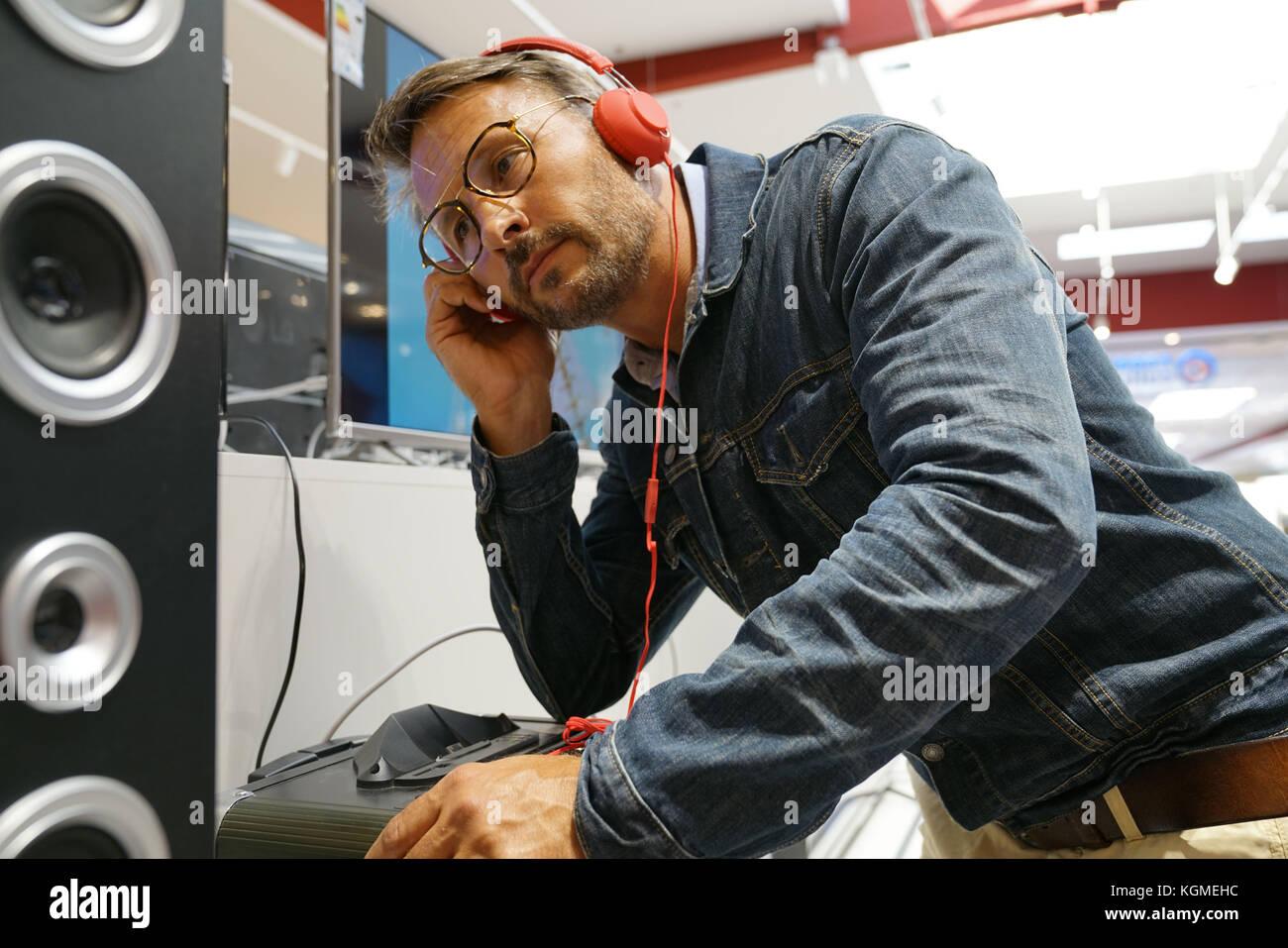 Hombre en pruebas tienda multimedia música con auriculares Imagen De Stock