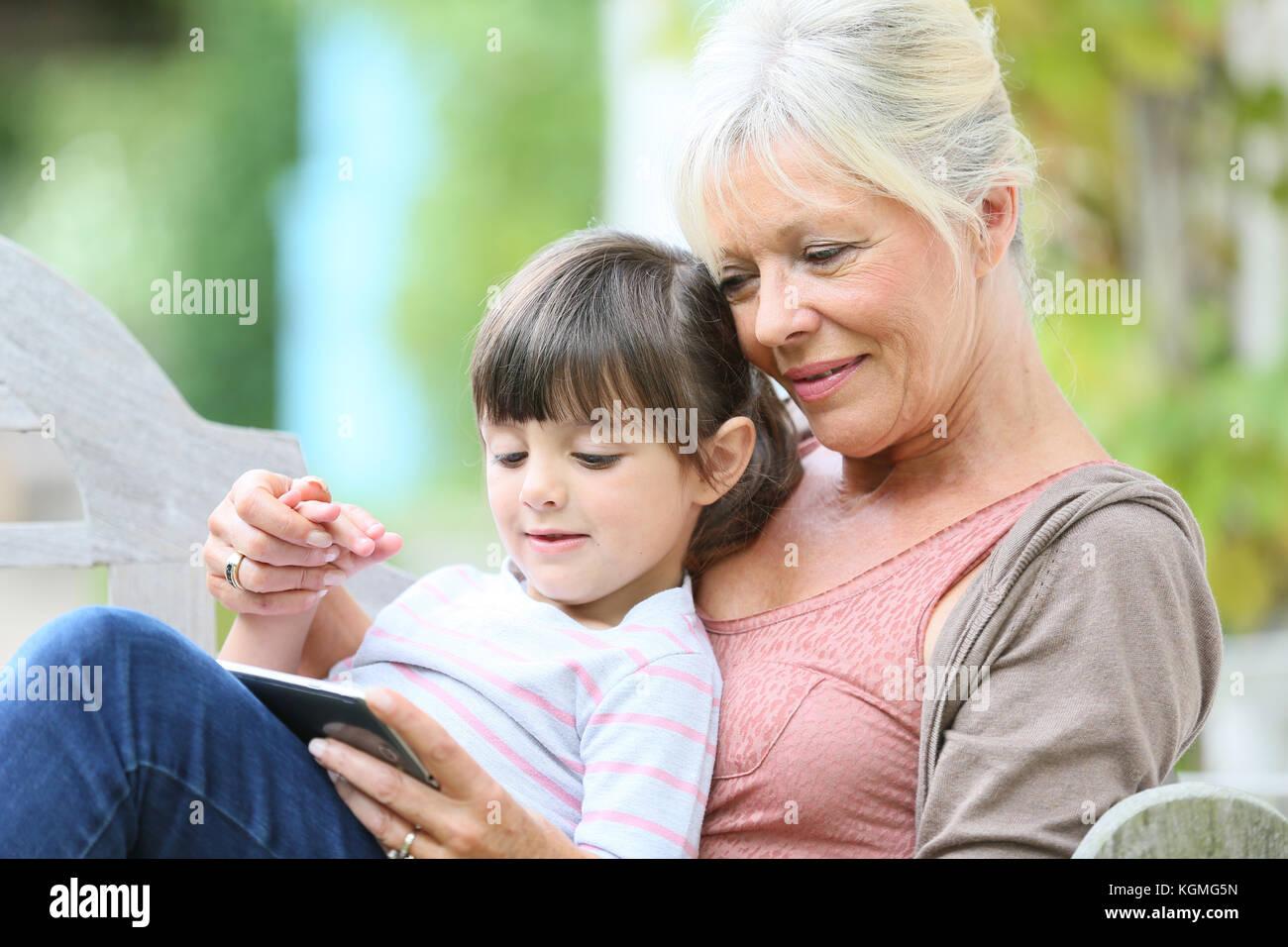 Mujer con grandkid senior jugando en smartphone Imagen De Stock