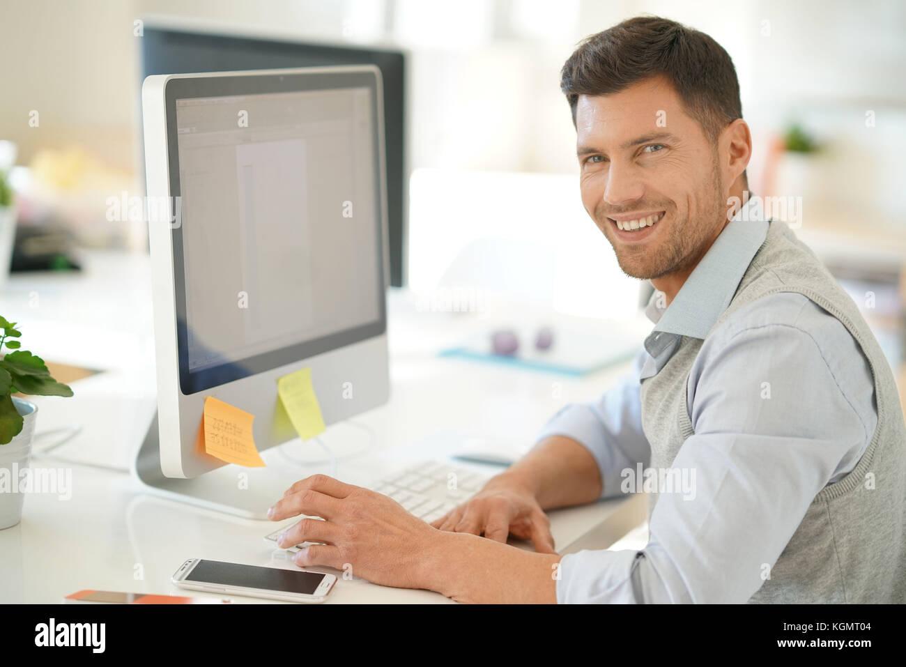 Guapo empresario trabajando en el equipo de escritorio en la oficina Imagen De Stock