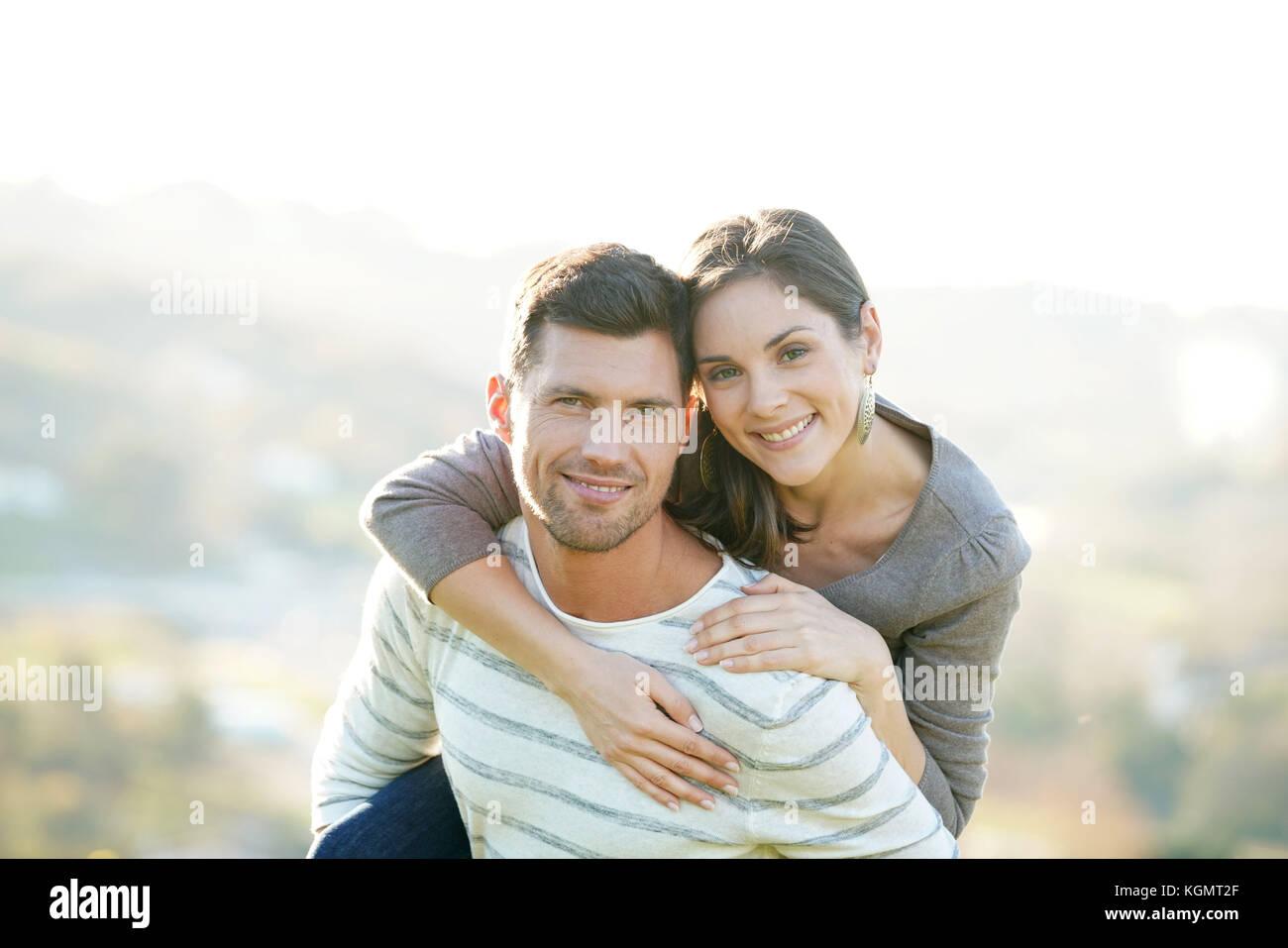 Retrato del hombre alegre dando piggyback ride para novia Imagen De Stock