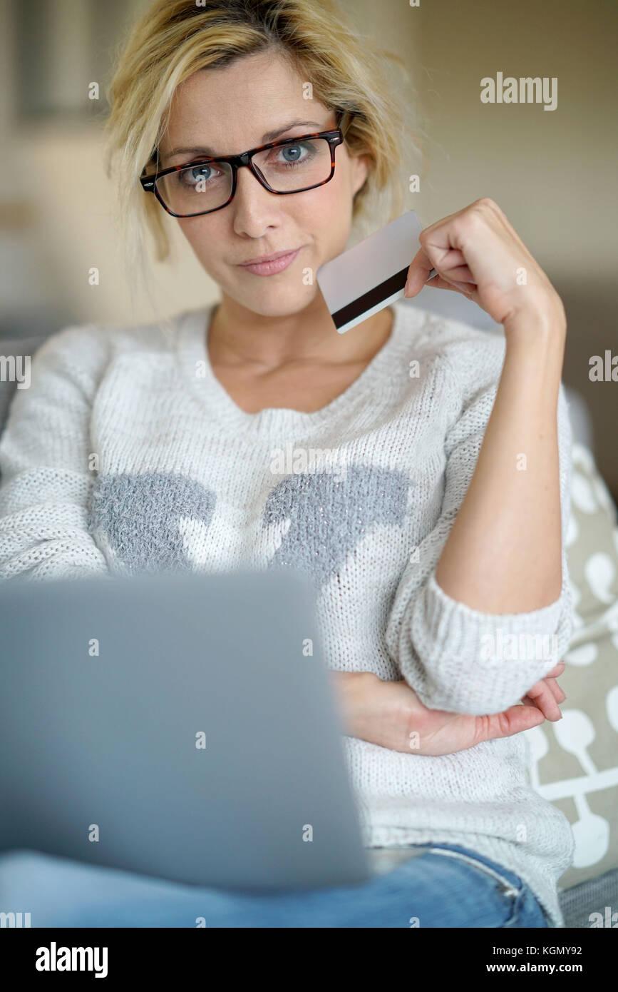 Mujer de mediana edad en casa, comprar en internet con tarjeta de crédito Imagen De Stock