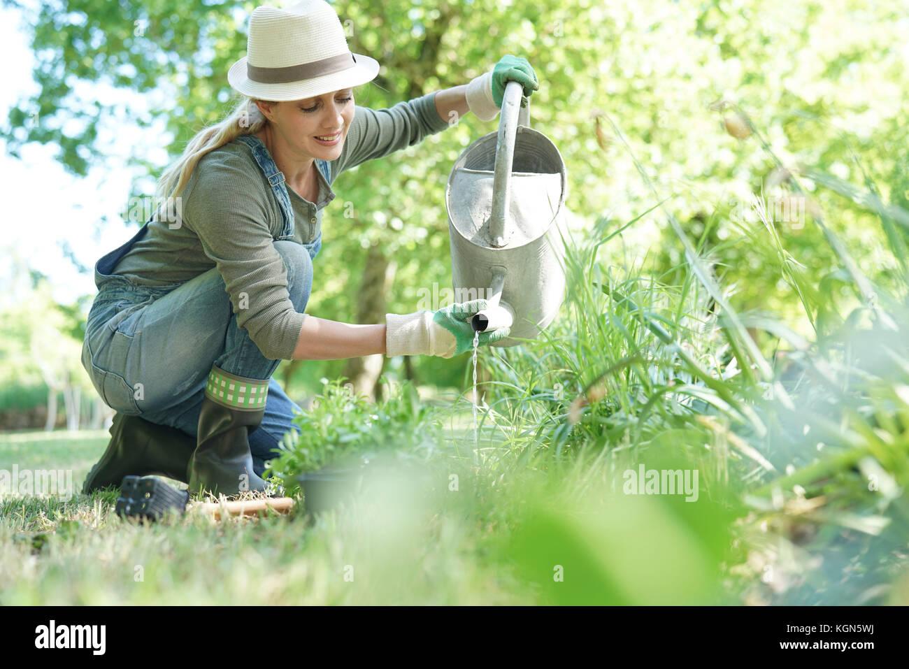Mujer rubia con sombrero jardinería Foto de stock