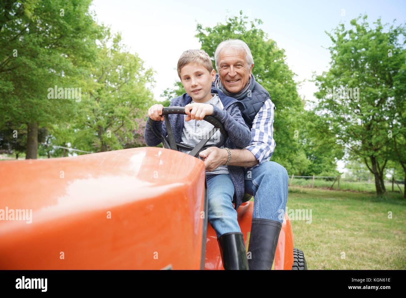 Hombre senior con grandkid cabalgando sobre cortadora de césped Imagen De Stock