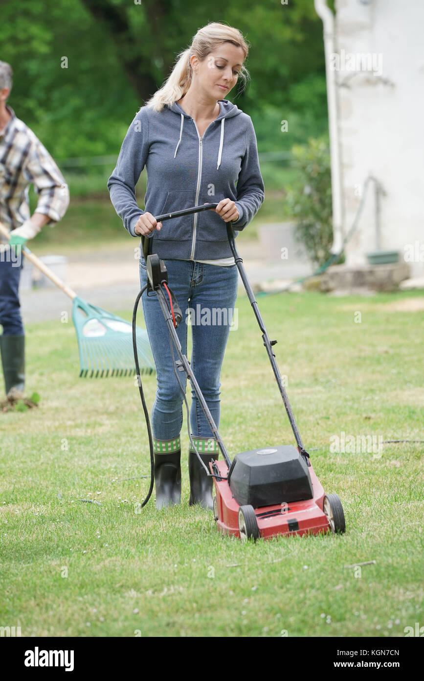 Mujer en el jardín cortando el césped Foto de stock