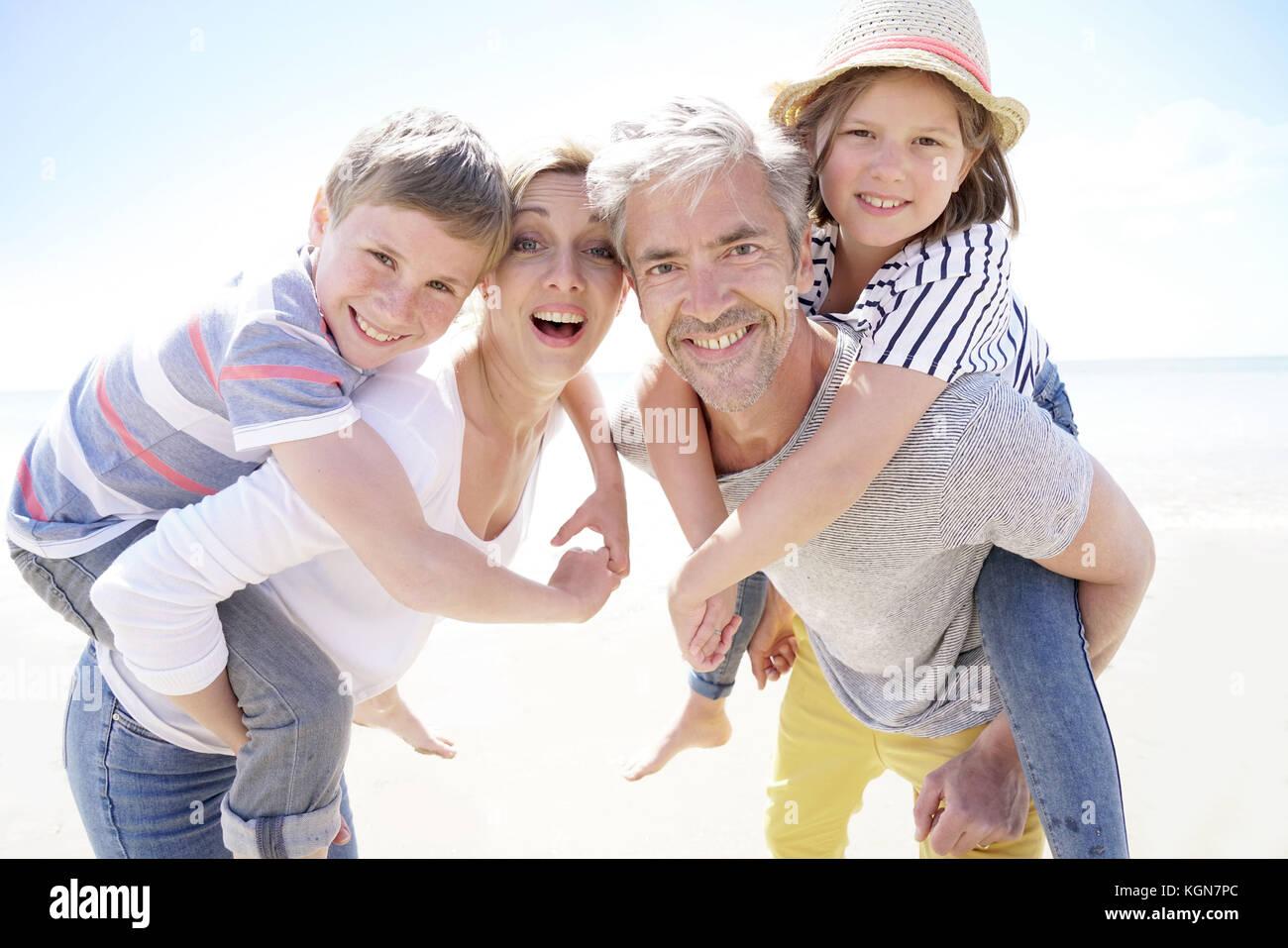Los padres dando piggyback ride para niños en la playa. Imagen De Stock