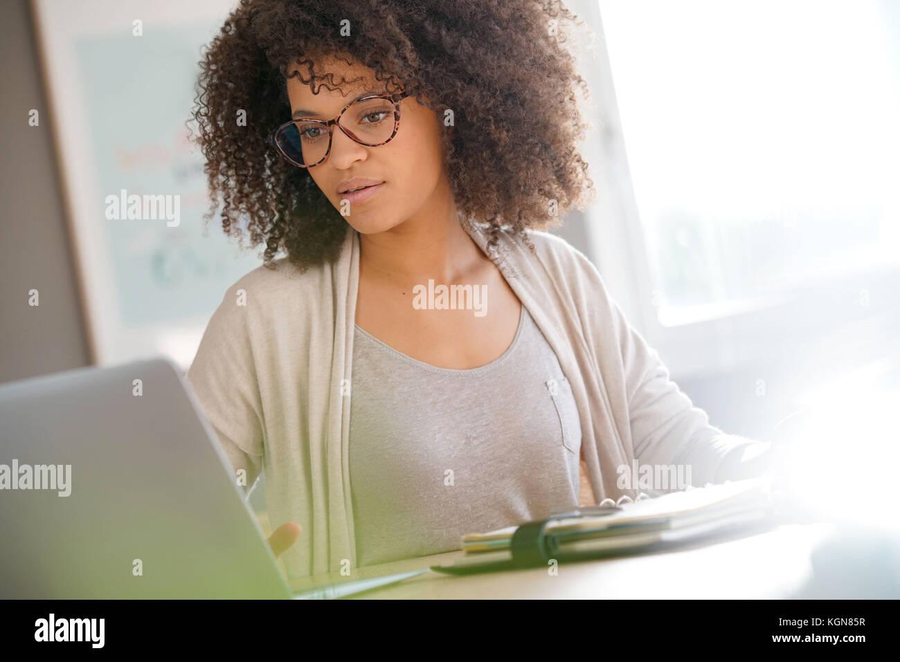Mujer de raza mixta trabaja desde casa en el ordenador portátil Imagen De Stock
