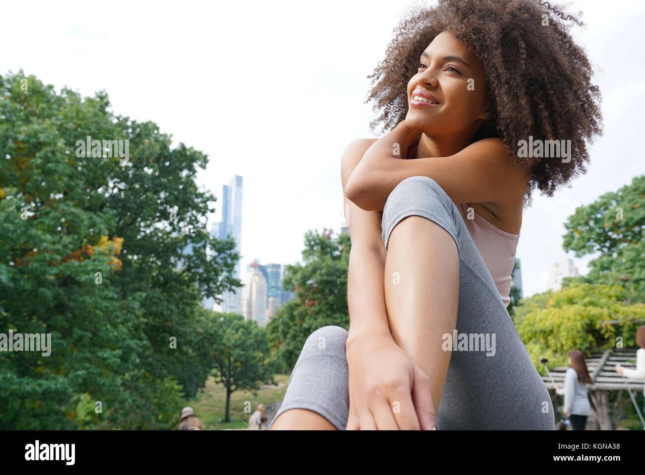 Bella mujer haciendo ejercicios de relajación en el parque central Imagen De Stock