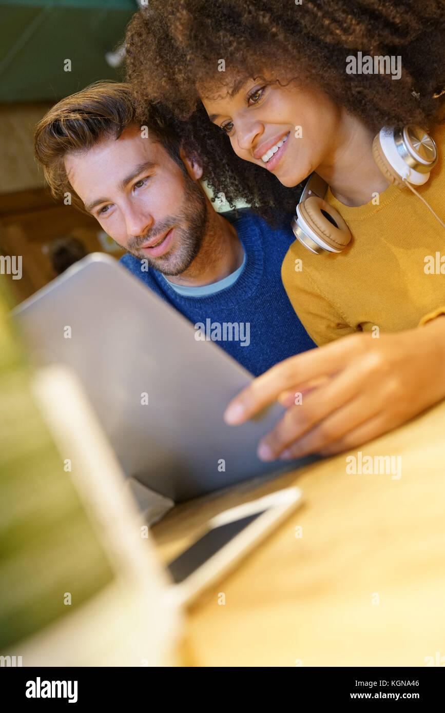 Pareja en restaurante conectados en internet con portátil Imagen De Stock