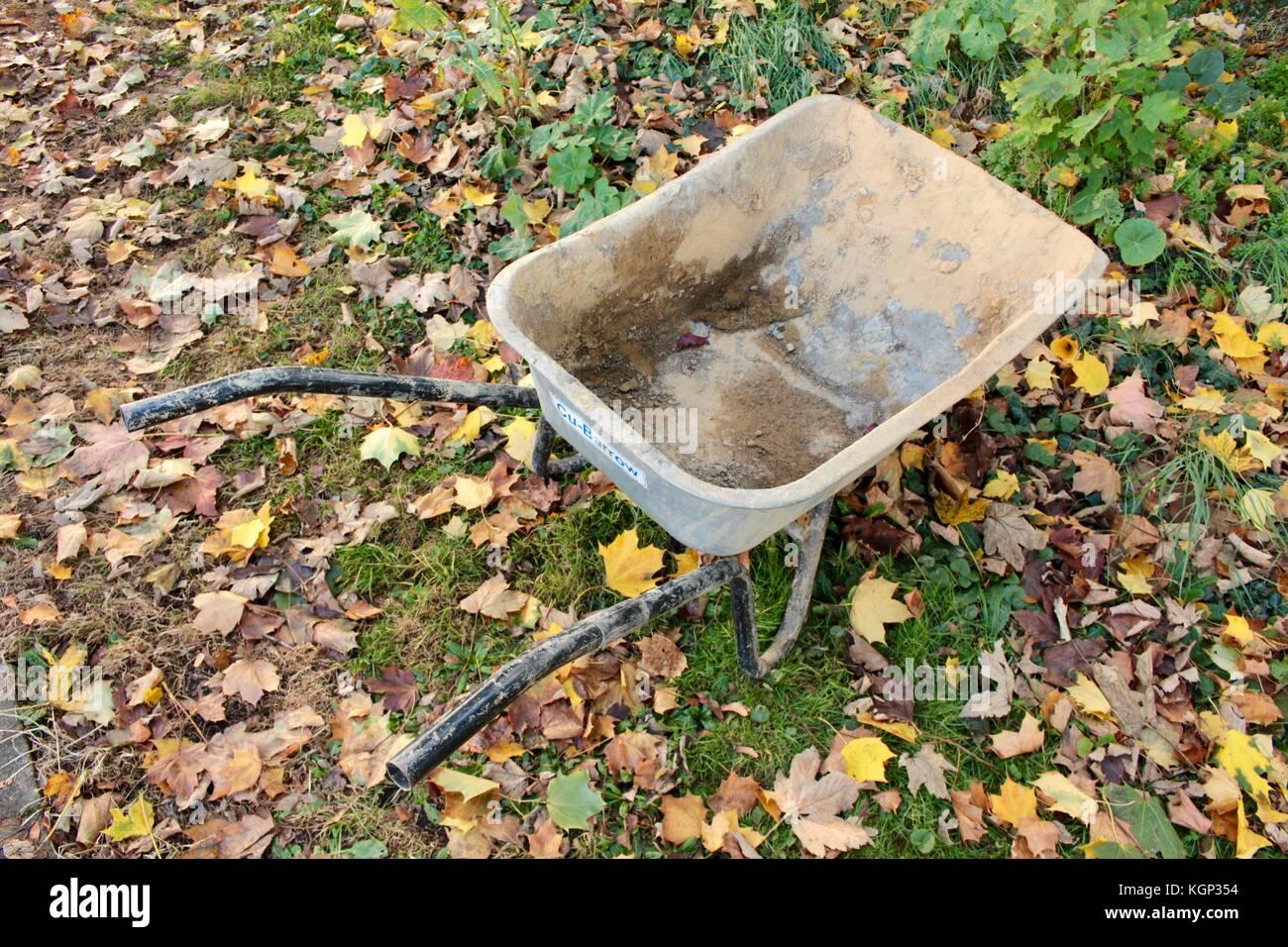 Carretilla de mano izquierda vacía constructores antiguos en otoño el jardín de césped sembrado en la hoja. Foto de stock