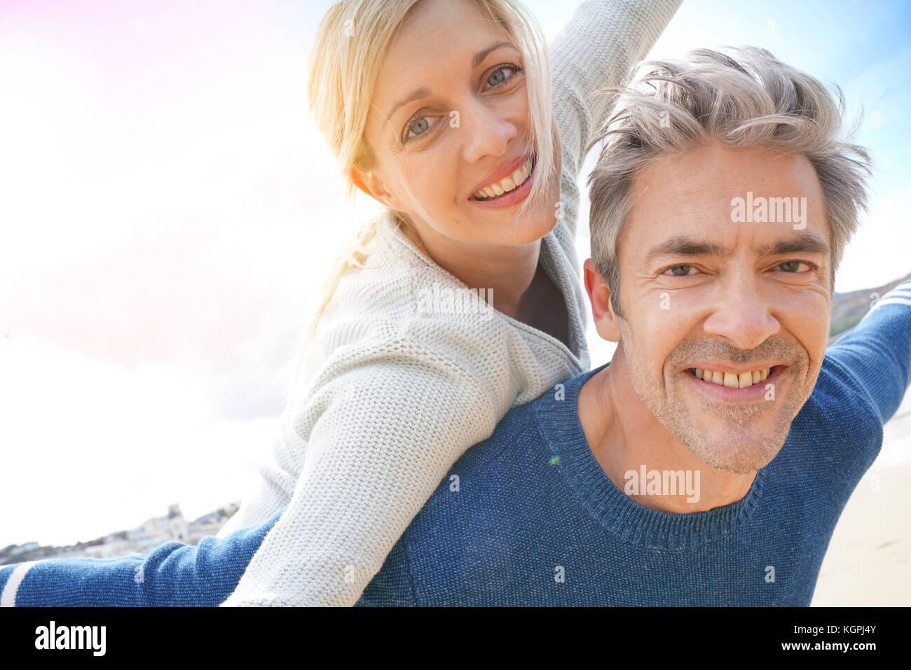 Hombre haciendo piggyback ride a mujer en la playa. Imagen De Stock