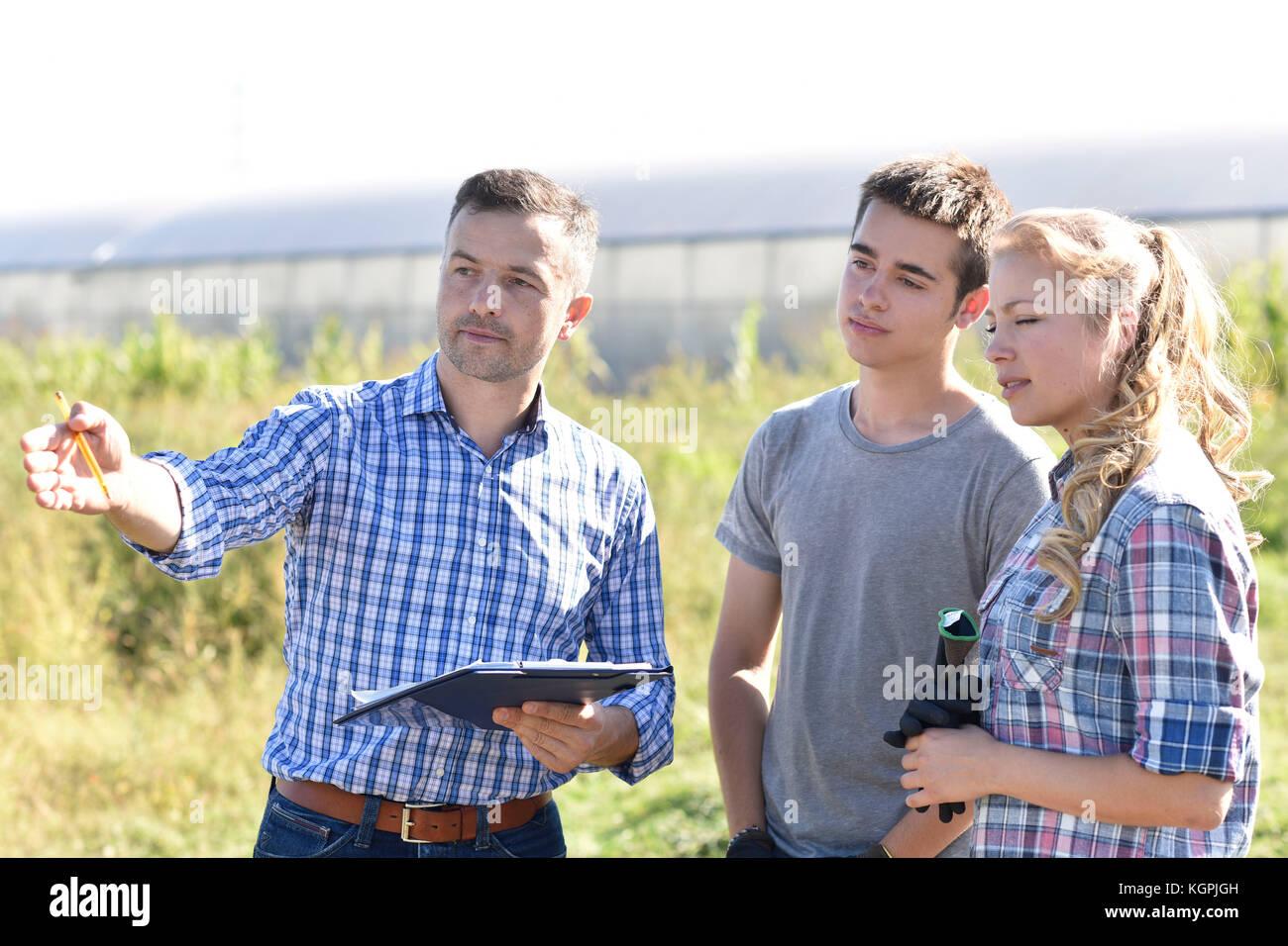 Los jóvenes con instructor en terreno agrícola Imagen De Stock