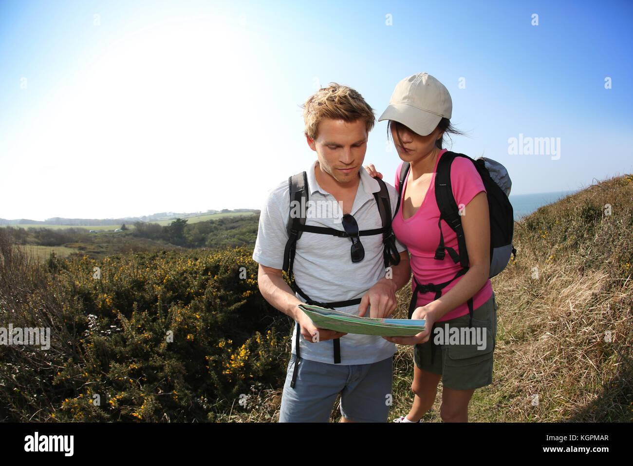 Los excursionistas en el país buscando la ruta en el mapa Imagen De Stock
