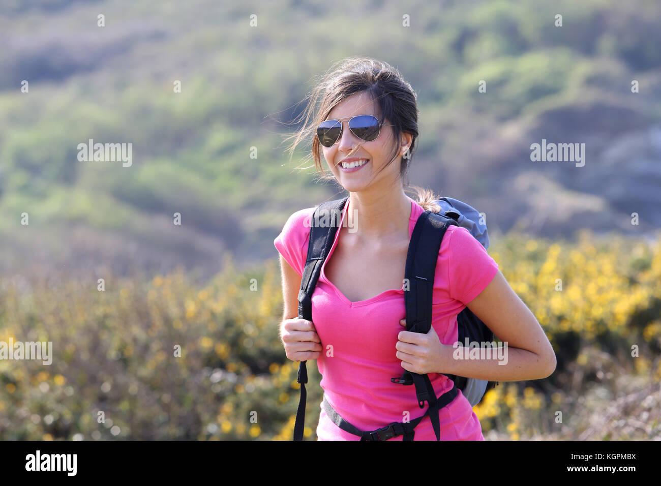 Caminante sonriente chica caminando en la ruta del país Imagen De Stock