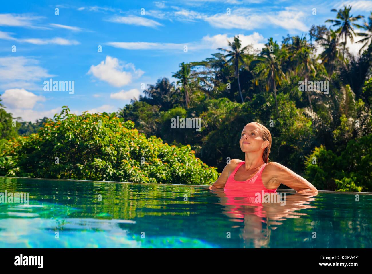 Mujer en la playa en verano, vacaciones en el lujoso hotel spa en la piscina desbordante con vistas a la jungla Imagen De Stock
