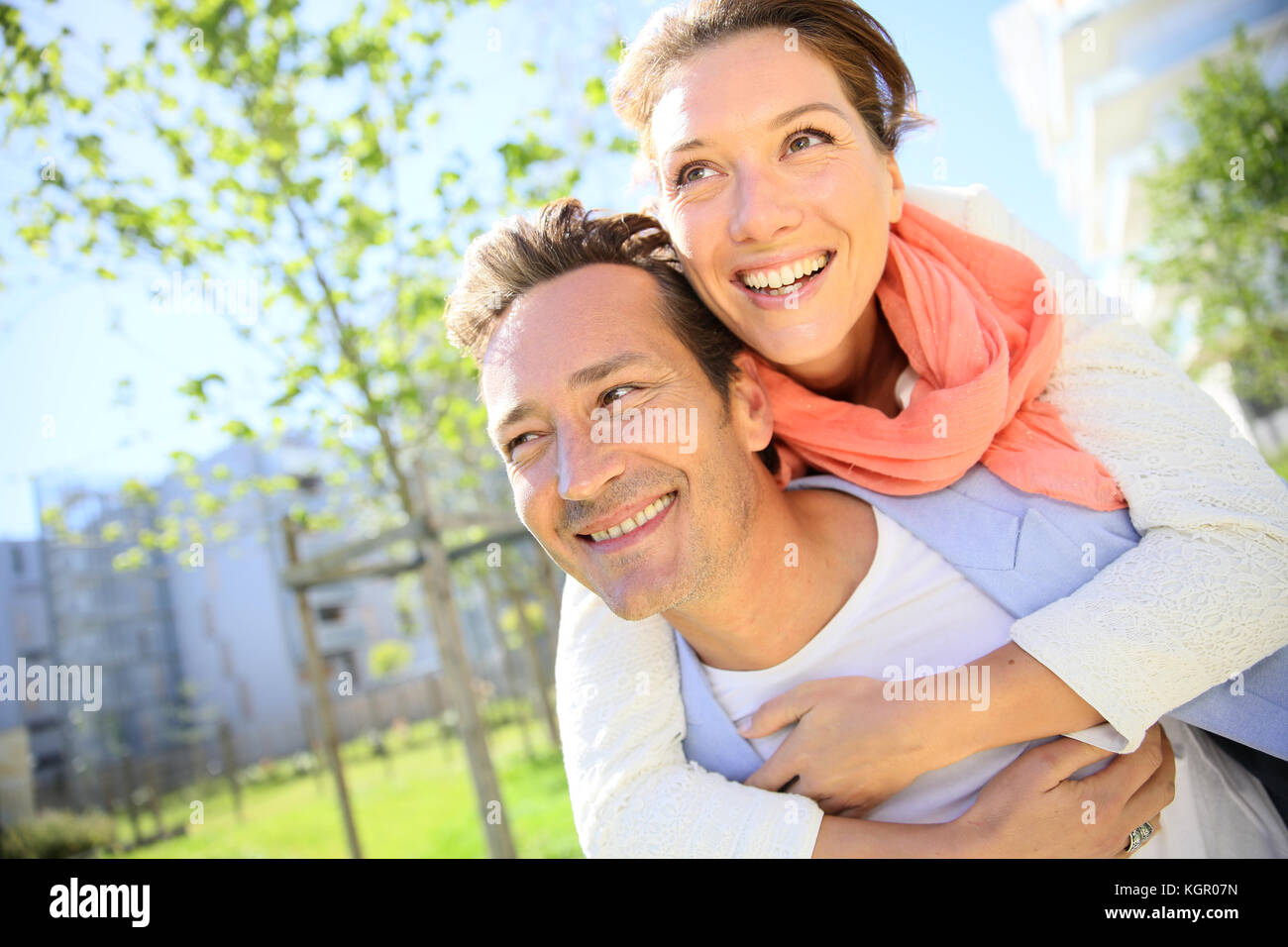 Hombre haciendo piggyback ride a mujer en estacionamiento Imagen De Stock