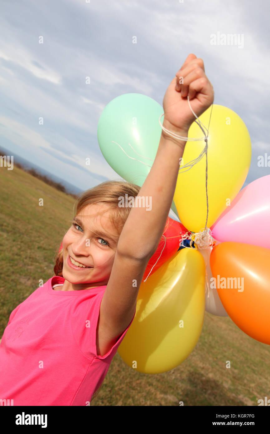 Niña la celebración de globos en la campiña Imagen De Stock