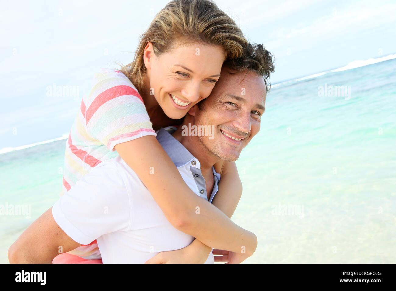 Hombre haciendo piggyback ride a la novia en la playa. Imagen De Stock