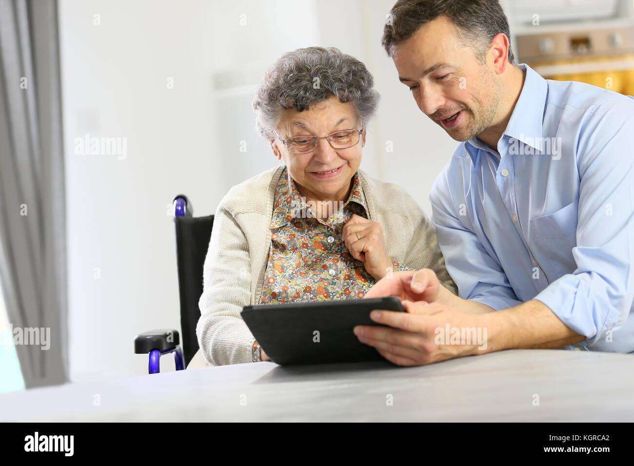 Hombre con anciana mediante tableta digital Foto de stock