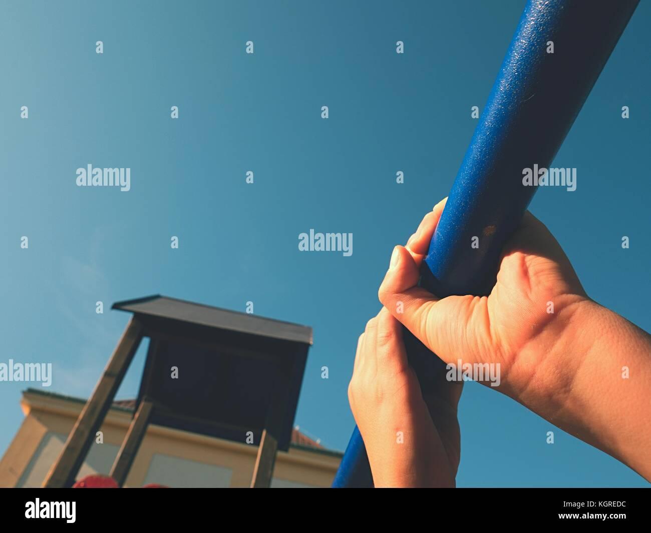 Agárrate a las barras de mono en playground. kid es la celebración de la barra de acero azul sobre la Imagen De Stock