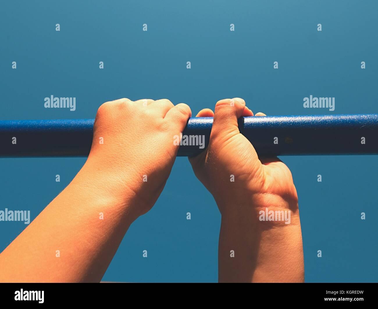 Chico manos sosteniendo en acero azul en el patio exterior, blue sky en segundo plano. Imagen De Stock