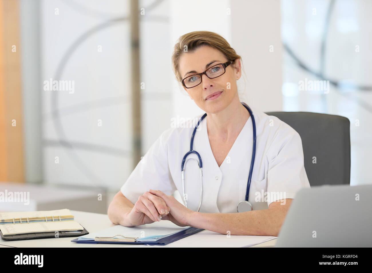 Retrato de enfermera madura sentados frente al escritorio en la oficina Imagen De Stock