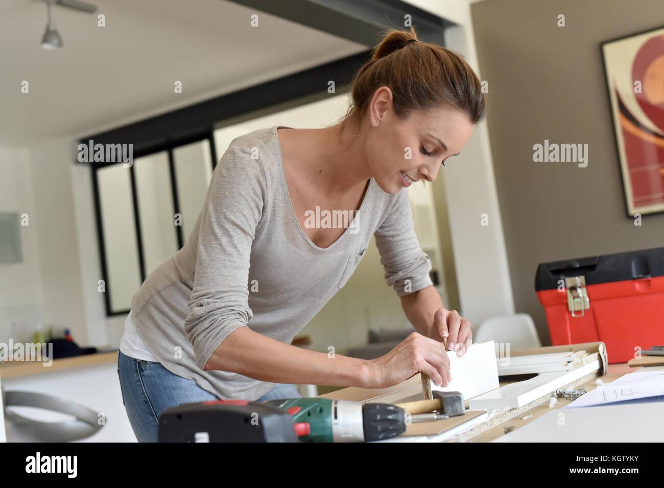 La mujer en el hogar montaje de muebles nuevos Imagen De Stock