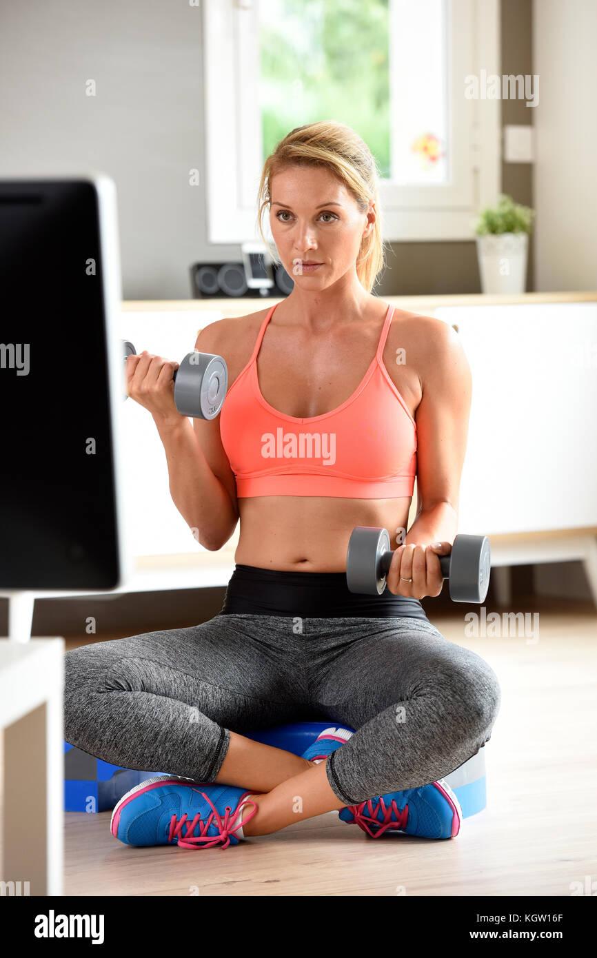 Chica fitness levantando pesas en frente de un programa de televisión Imagen De Stock