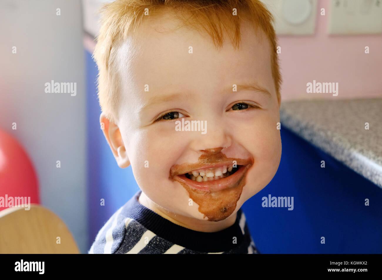 Un joven muchacho feliz, sonriendo ampliamente, su rostro cubierto de helado de chocolate habiendo comido y un helado de chocolate tratar Foto de stock