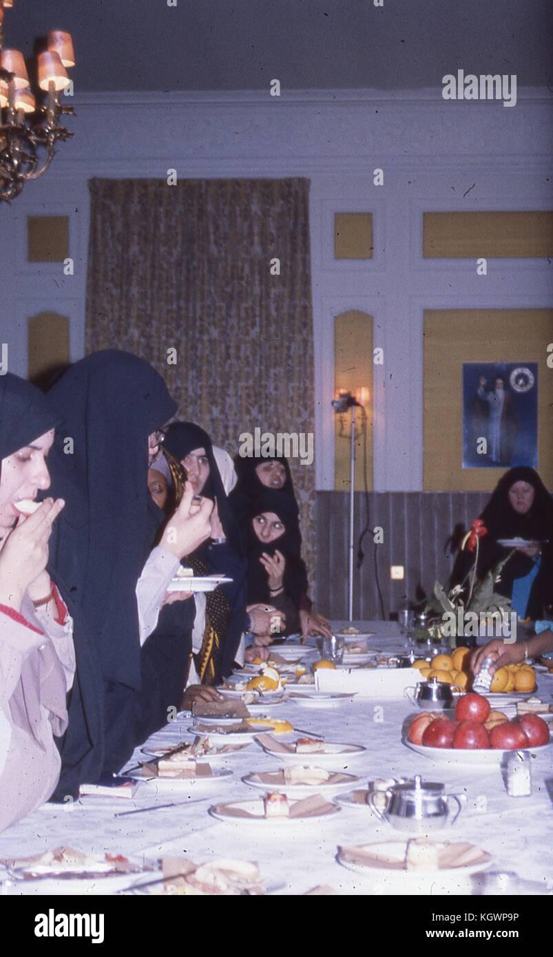 Escena de un grupo de mujeres musulmanas de diversas etnias vistiendo chadri, comiendo torta y fruto de una larga Imagen De Stock