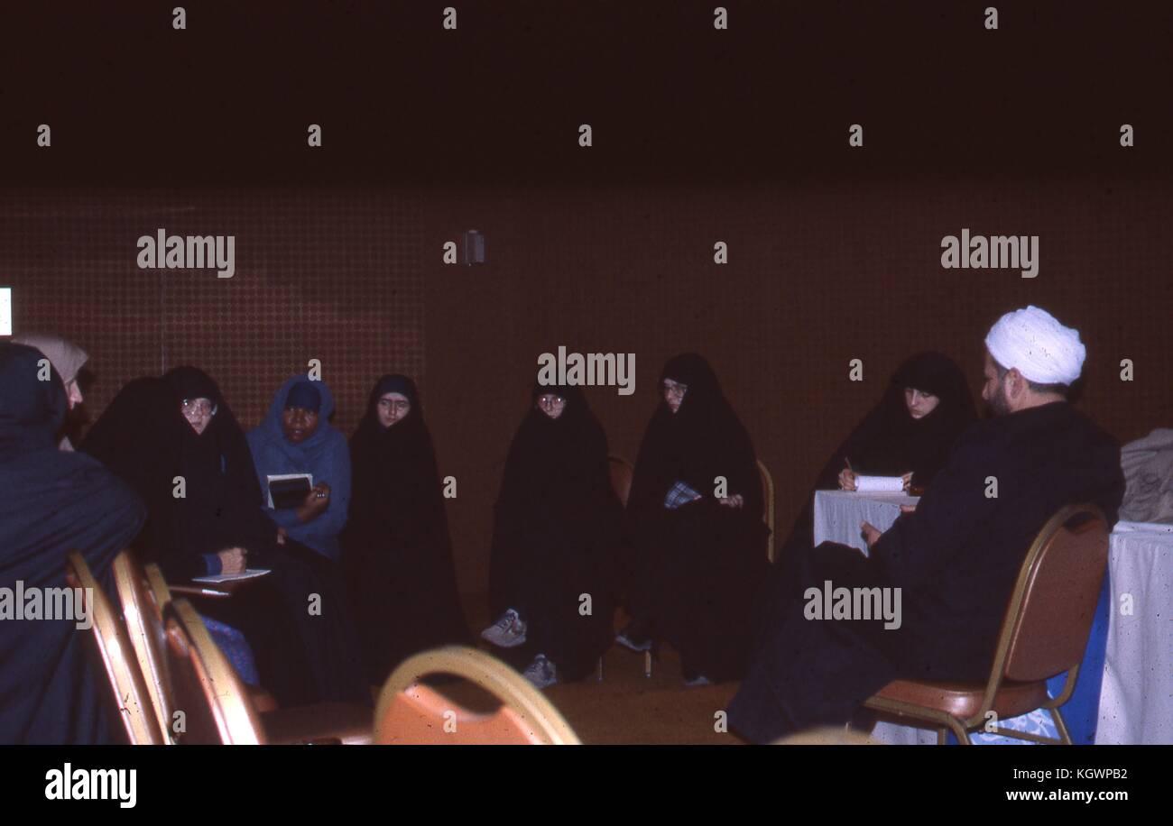 Escena de mujeres musulmanas de diversas etnias vestida con chadri, sentados en círculo tomando notas, en un Imagen De Stock