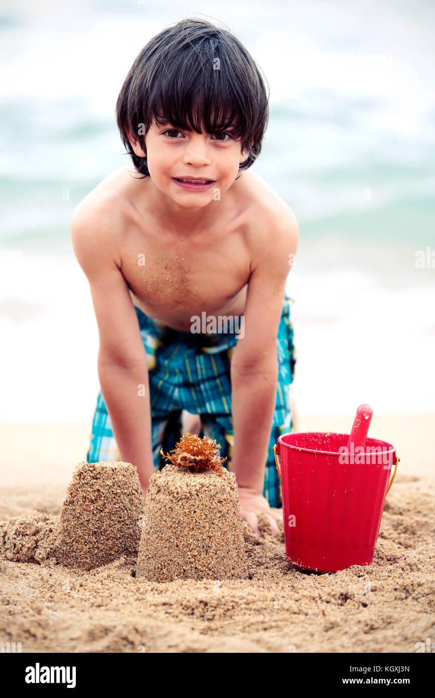 Niño jugando en la arena de una playa en España Imagen De Stock