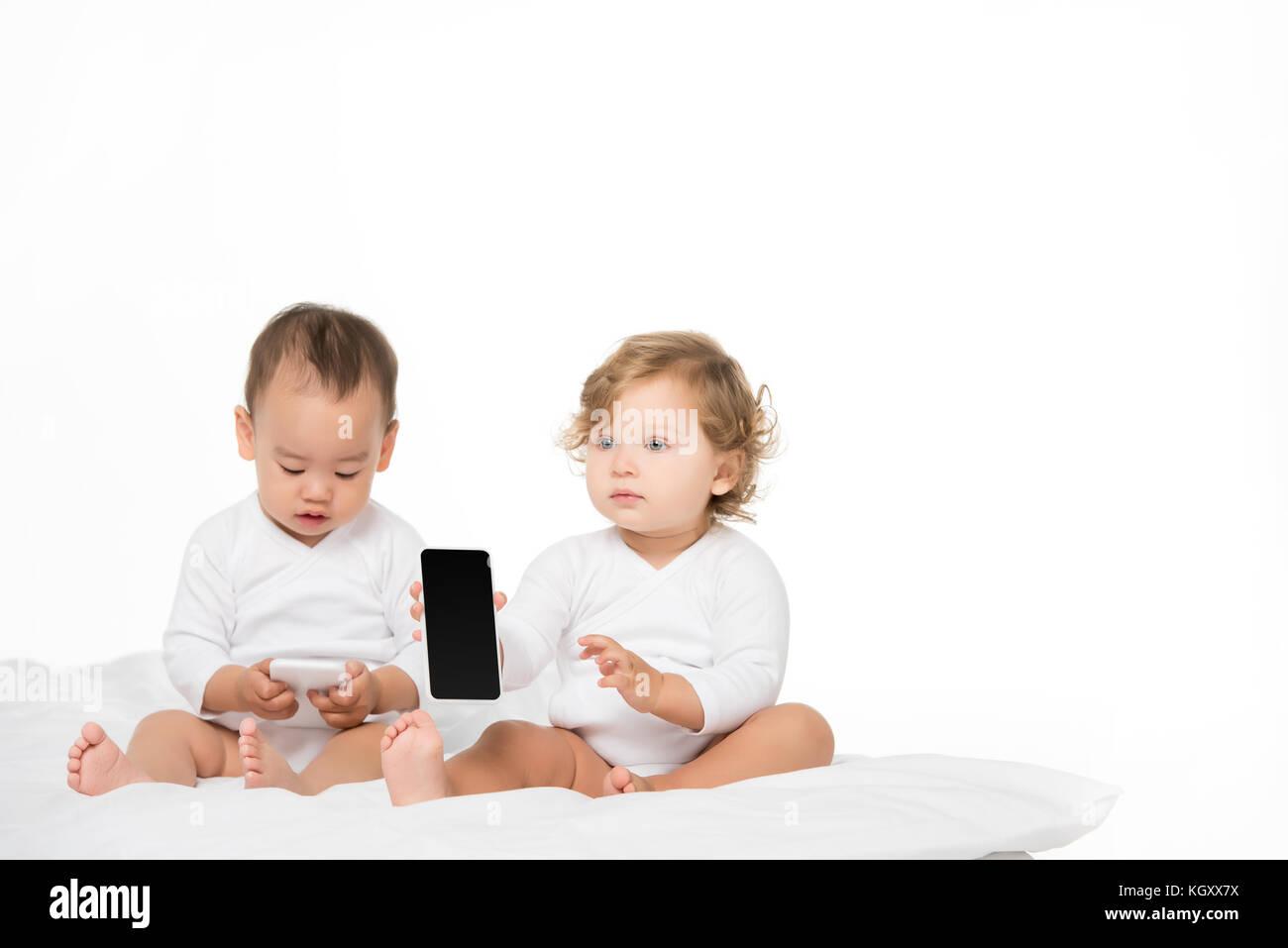 Los niños multiculturales con smartphones digital Foto de stock
