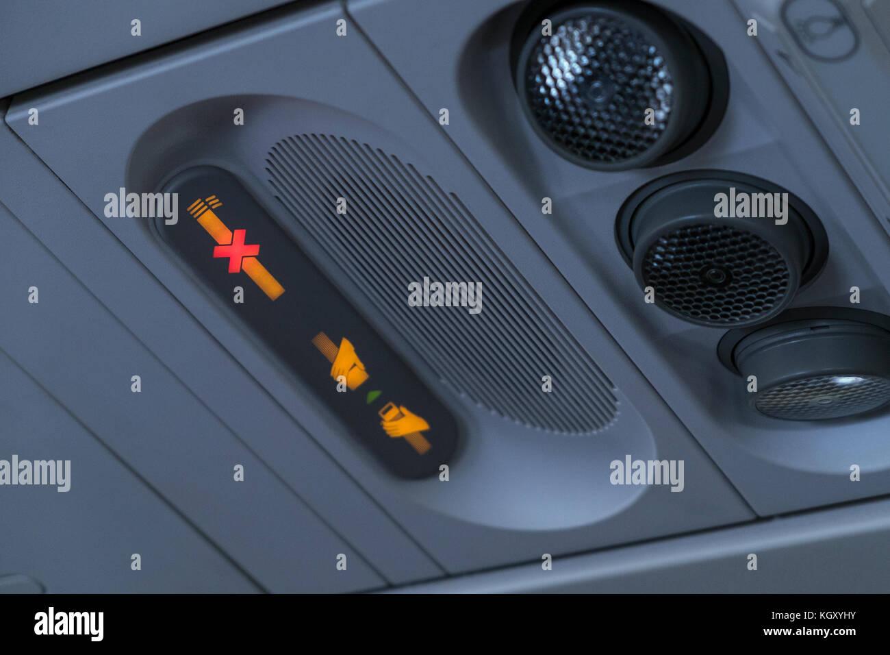 No fumar y abrocharse el cinturón encendido símbolos en la parte superior de la pantalla por encima de asientos Foto de stock