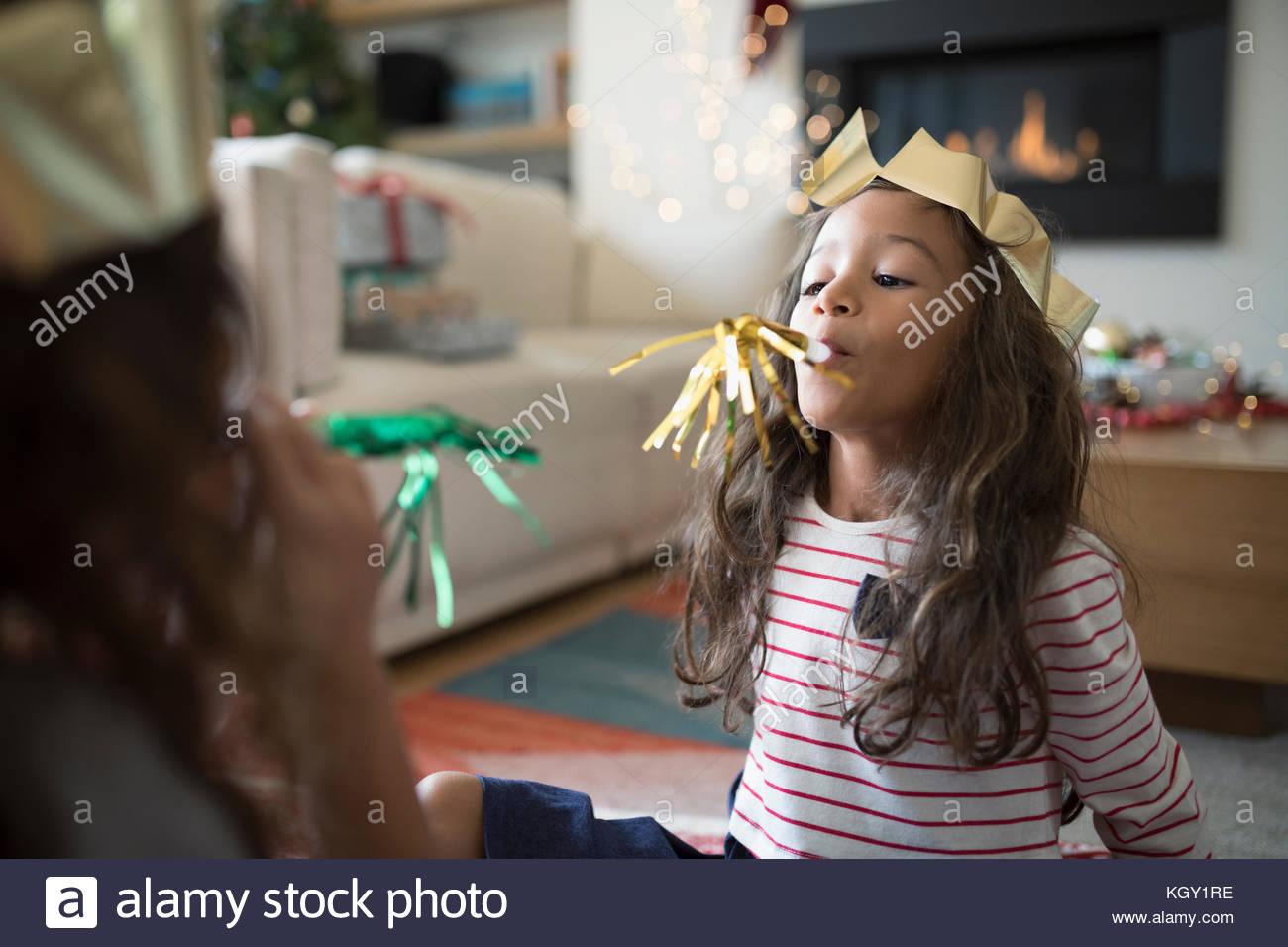 Hermanas en papel coronas de navidad jugando con los favores del partido Imagen De Stock