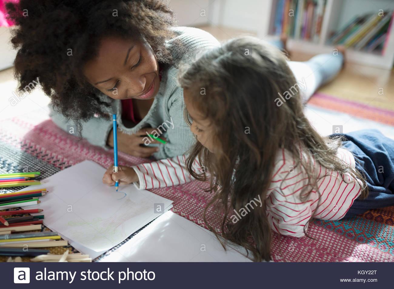 Madre e hija de dibujo con lápices de colores sobre una alfombra Imagen De Stock