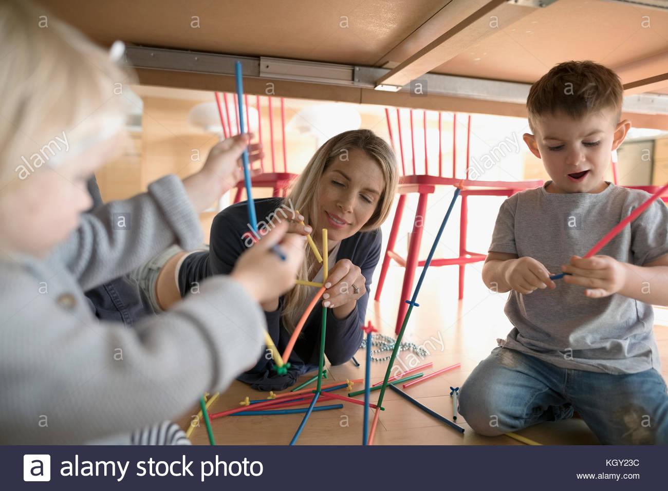 La madre y el niño los niños jugando con el conector palos bajo la mesa Imagen De Stock