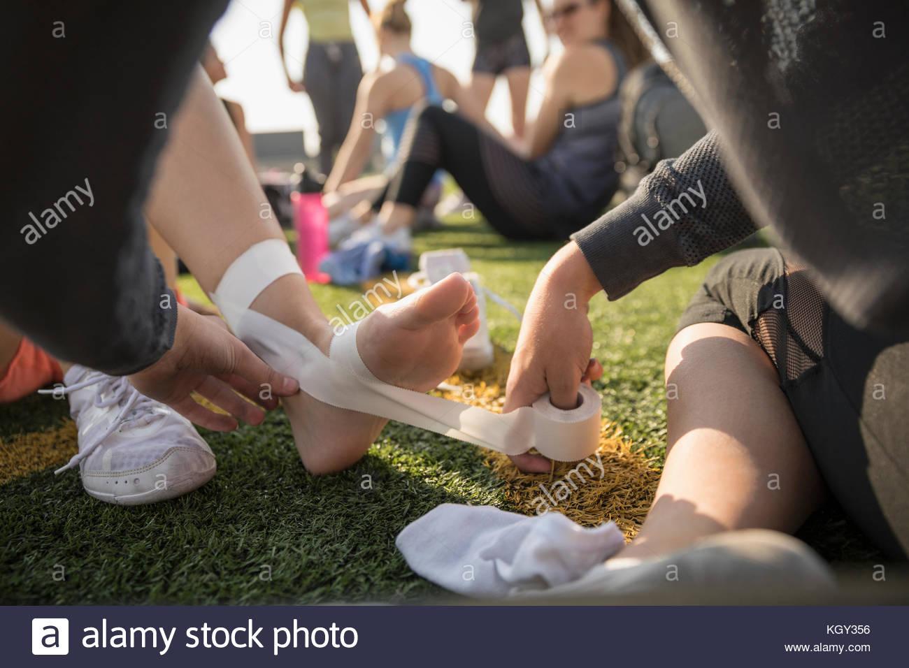 Adolescente high school equipo de animadoras encintar los pies y tobillos con cinta adhesiva. Imagen De Stock