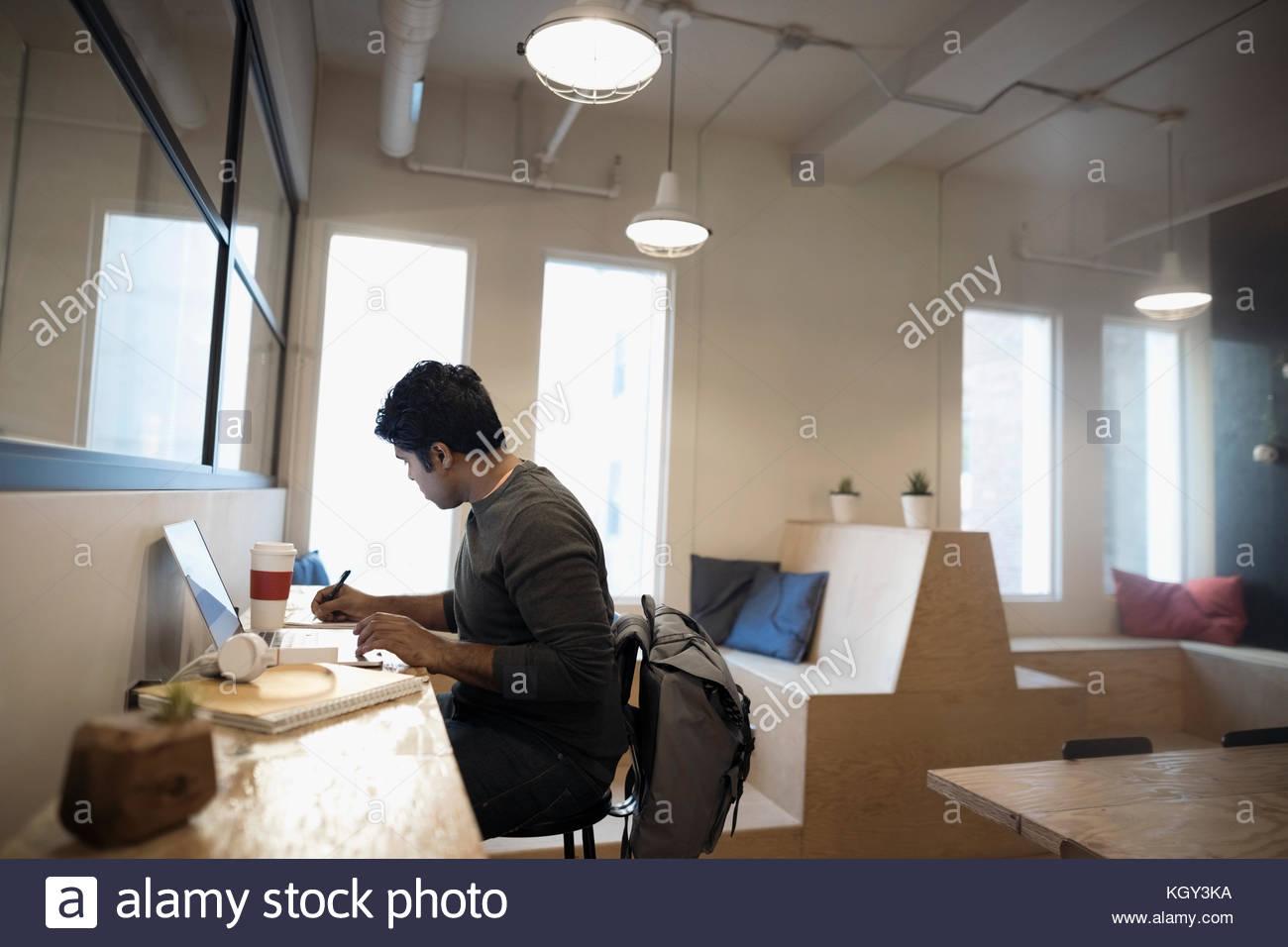 Diseñador masculino tomando notas, trabajando en el portátil en espacio de coworking office Imagen De Stock