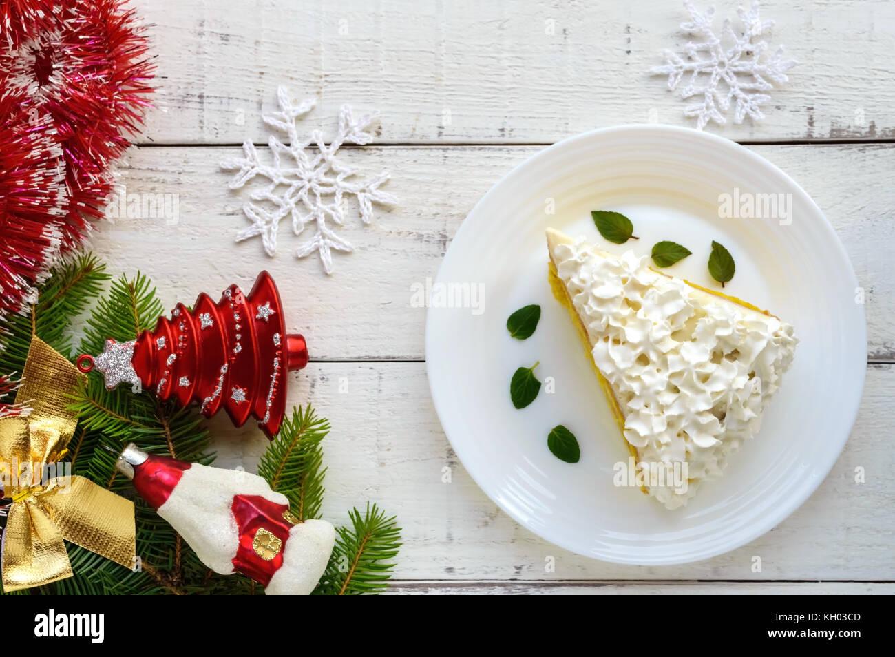 Un gran trozo de bizcocho delicada decoración crema postre aire festivo sobre un fondo blanco. Para celebrar Imagen De Stock
