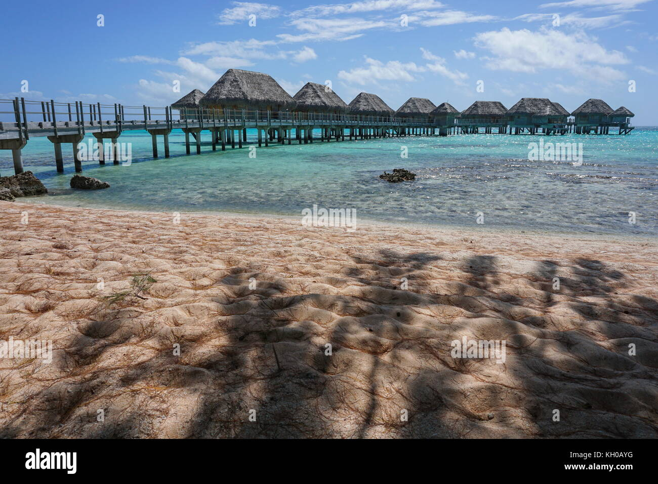 Laguna tropical con bungalows sobre el agua de un complejo visto desde una playa de arena a la sombra de los árboles, Foto de stock