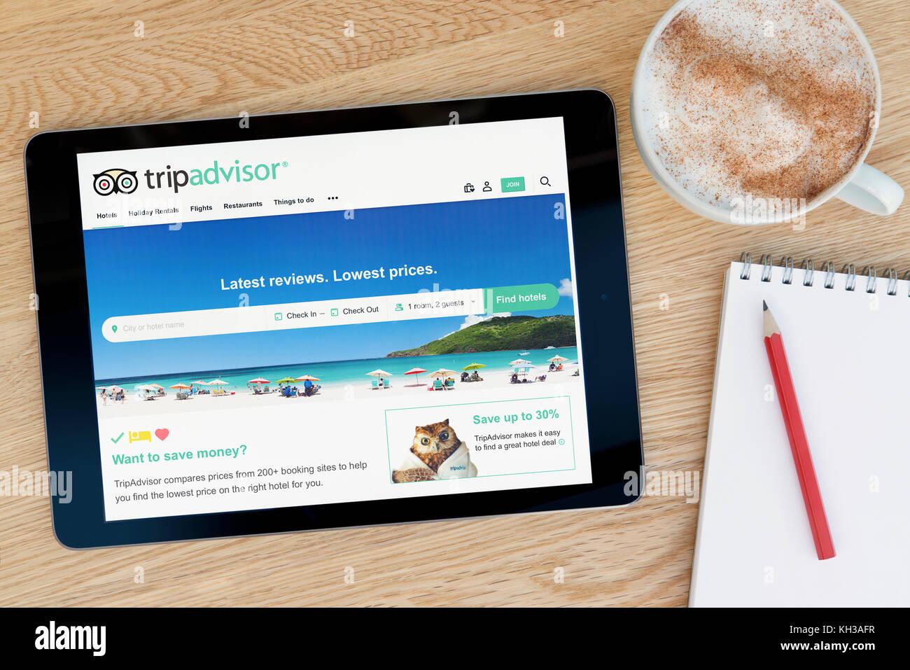 El sitio web de Tripadvisor características en un dispositivo tablet iPad que descansa sobre una mesa de madera Imagen De Stock