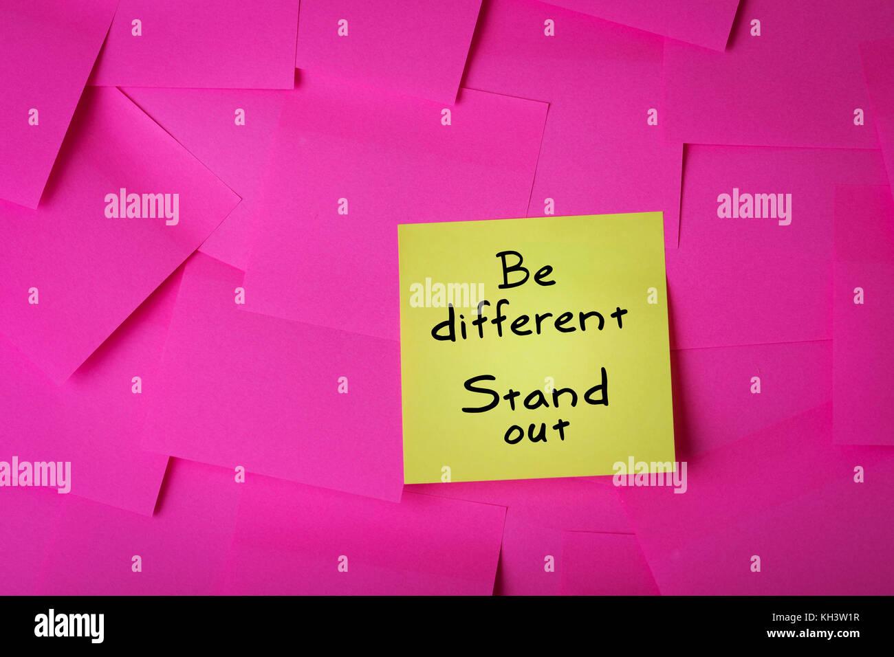 Ser diferente se destacan el texto de nota adhesiva amarilla Foto de stock