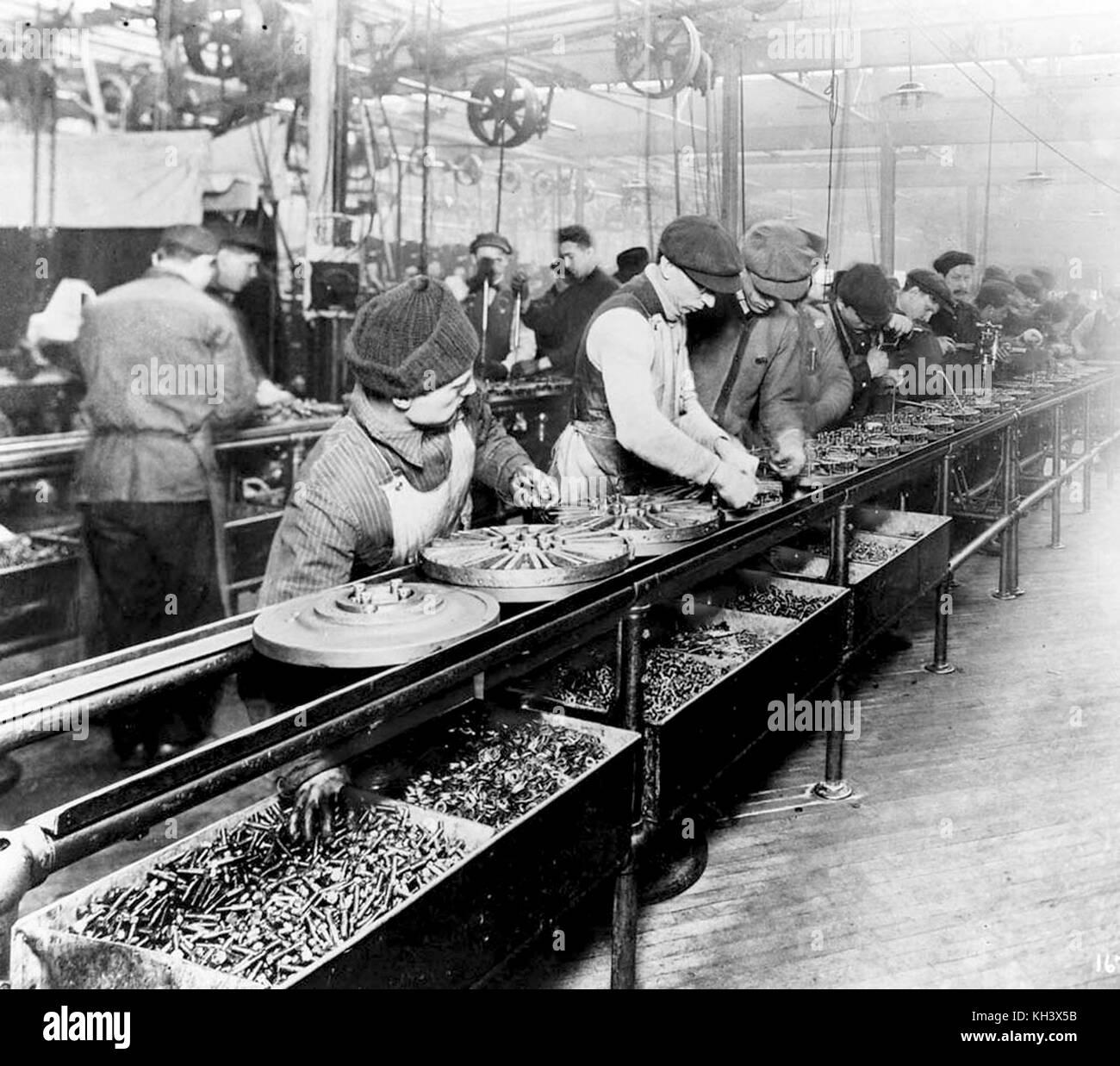 Los trabajadores de la primera línea de ensamblaje en movimiento juntos magnetos y volantes para autos Ford, Imagen De Stock