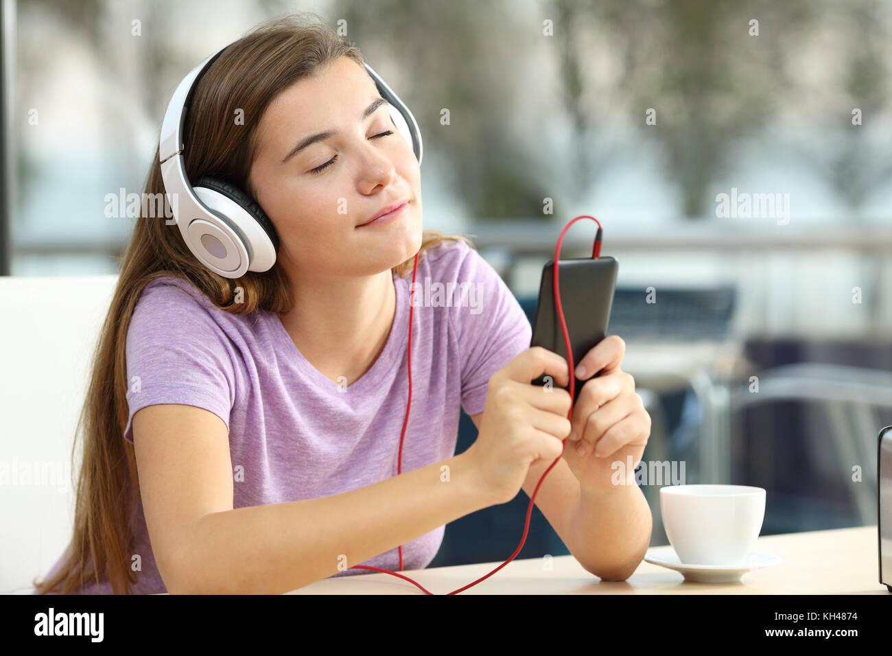 Retrato de una adolescente relajado escuchando música en un bar en la noche Imagen De Stock