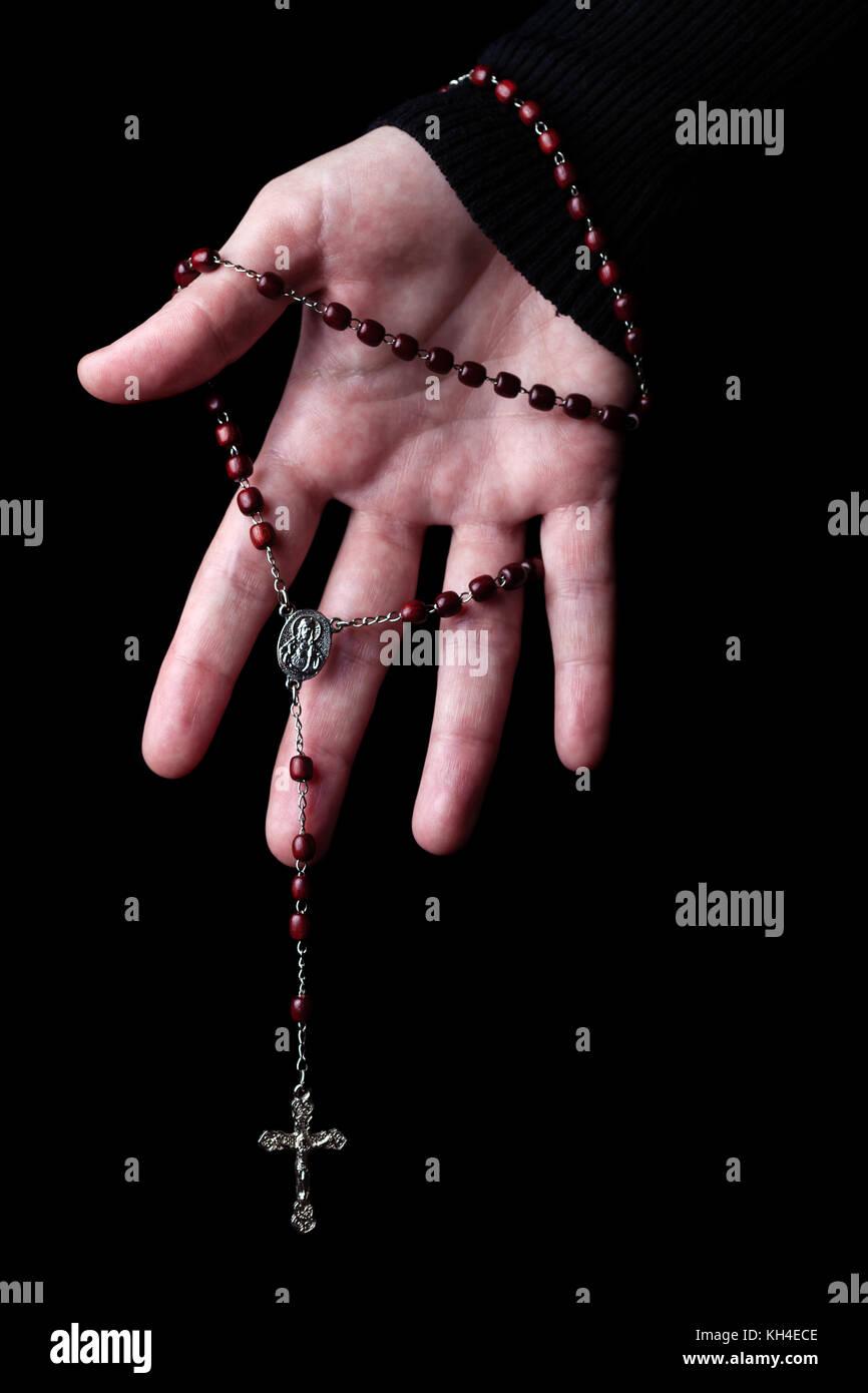 Mujeres manos sosteniendo y colgando un rosario con Jesucristo en la cruz o crucifijo sobre fondo negro. Mujer con Imagen De Stock