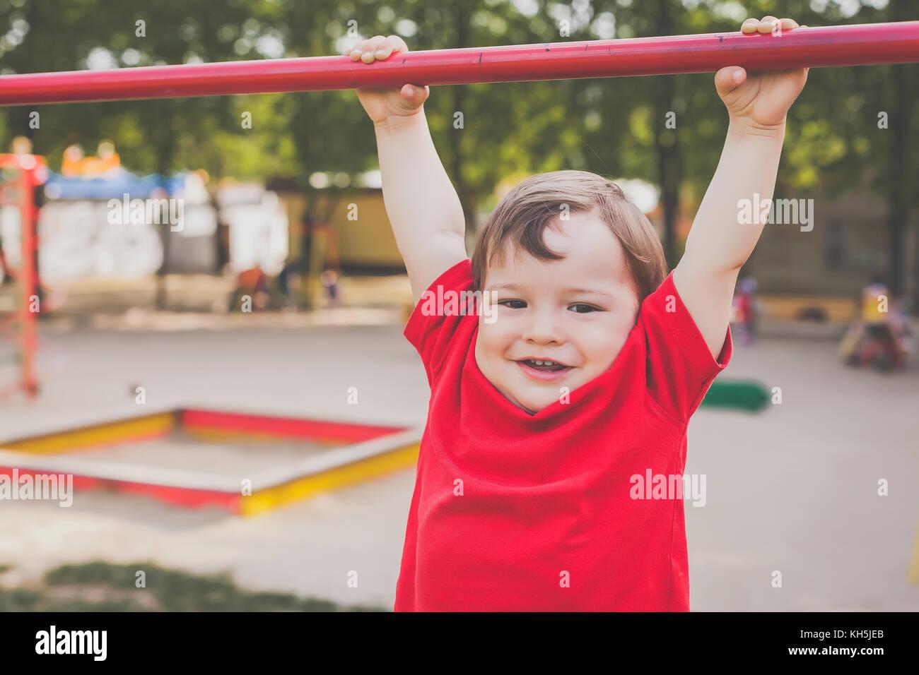 Retrato de chico lindo sonriente y jugando en el patio de recreo Imagen De Stock
