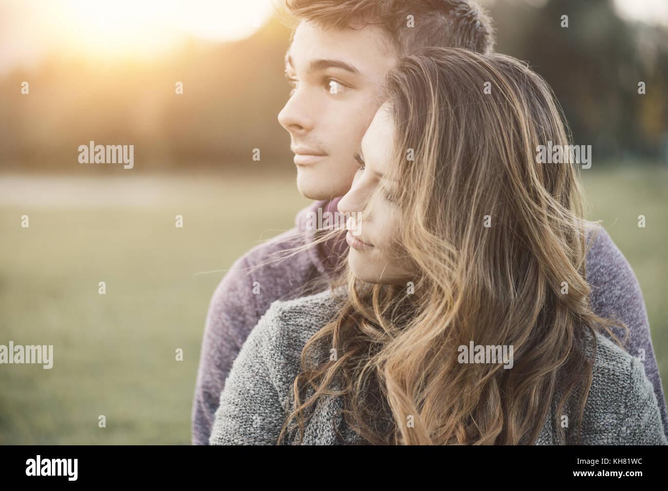 Joven pareja amorosa afuera, sentados en el césped, abrazándolo y mirar hacia el futuro, y el concepto Imagen De Stock