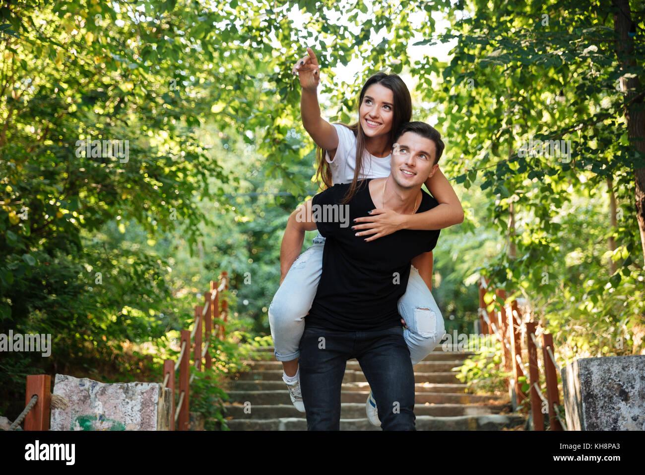 Joven pareja feliz disfrutando piggyback paseo en el parque al aire libre, mujer sonriente dedo señalador lejos Imagen De Stock