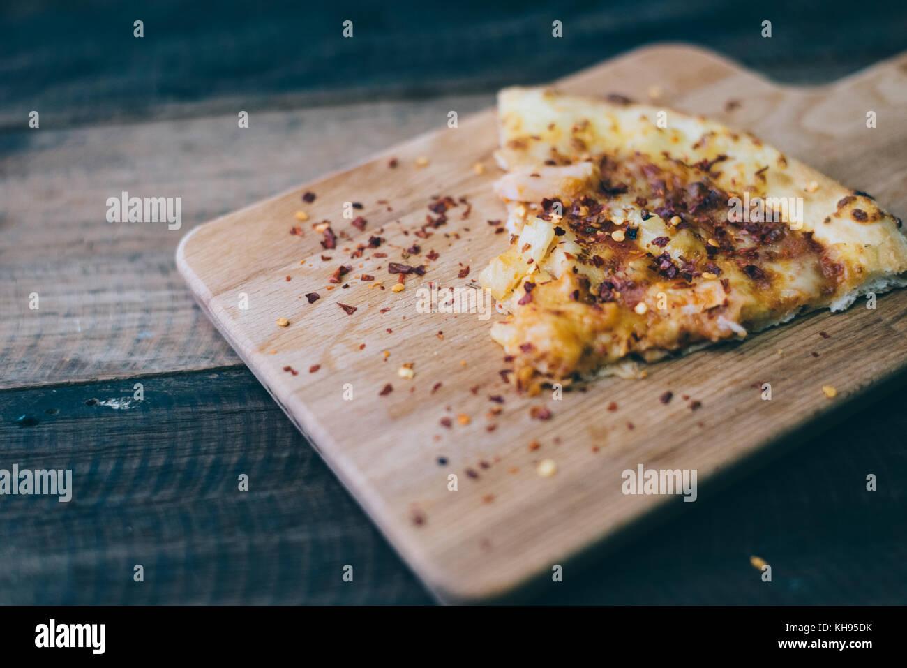 Slice de pizza con queso, carne de pollo y piña topping en una placa de madera/tabla.famosa comida italiana Foto de stock